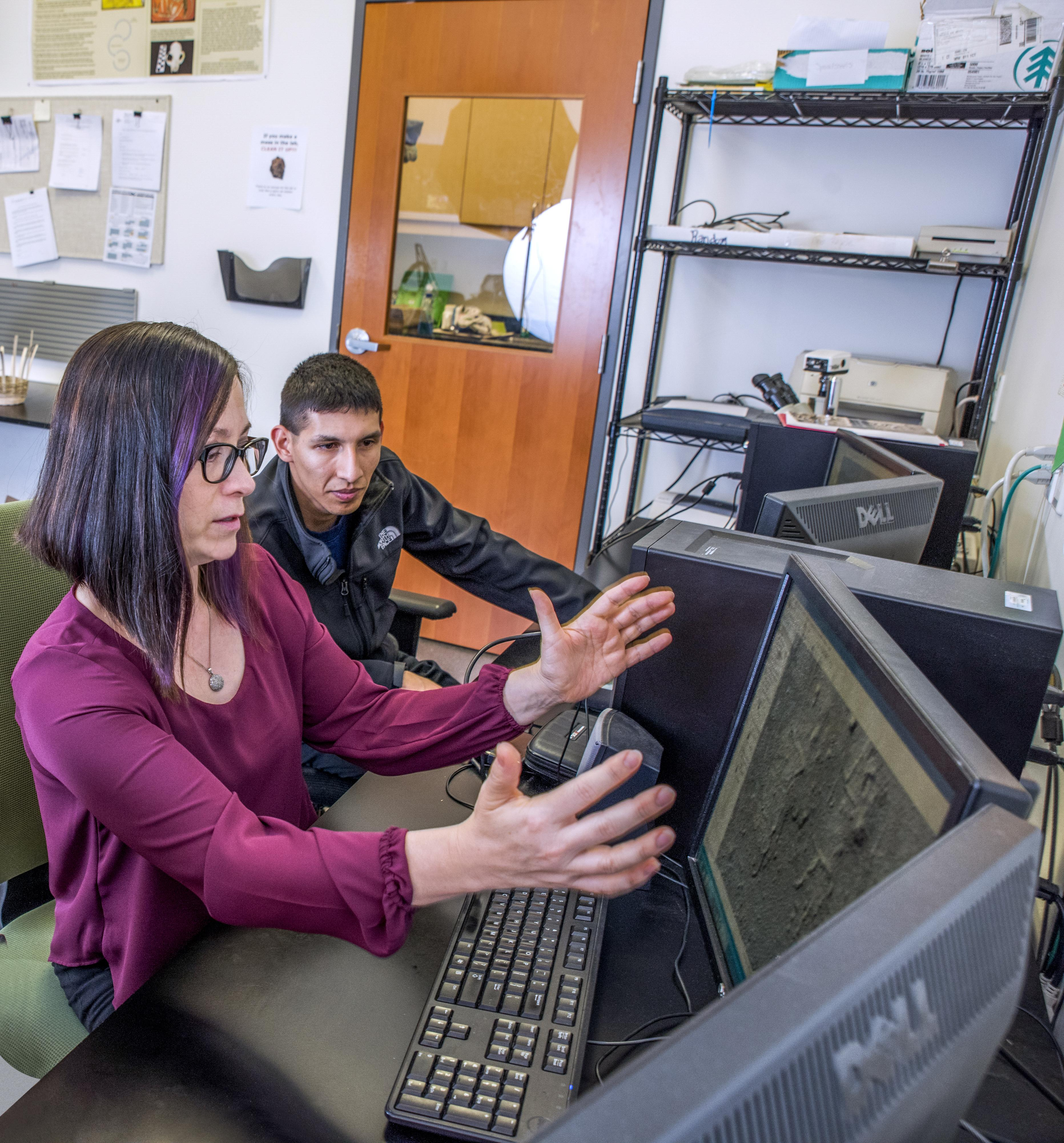 Dr. Marisol Cortes-Rincon working with a student at computer